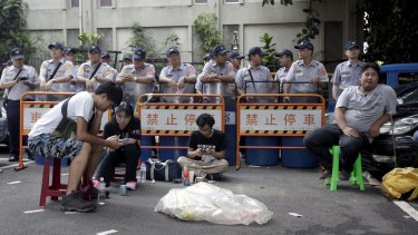 Police officers stand guard as students participate in a protest at the entrance to the Ministry of Education in Taipei on Friday.