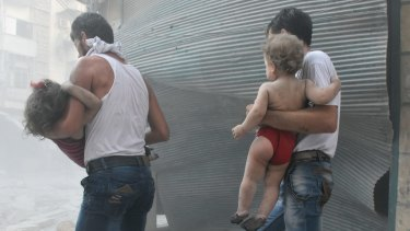 Syrians carry their children after the Syrian army carried out air strikes in Aleppo, Syria on August 13.