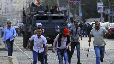 Crackdown: Police pursue protesters in Cairo in June 2014.