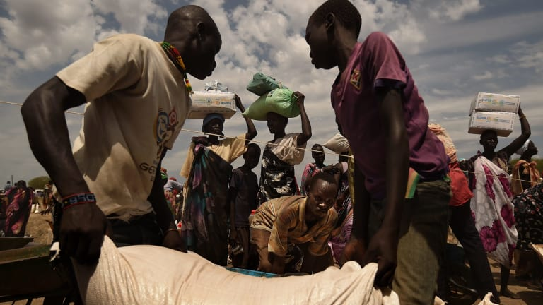 Refugees collect food in South Sudan, where famine was declared earlier this year.