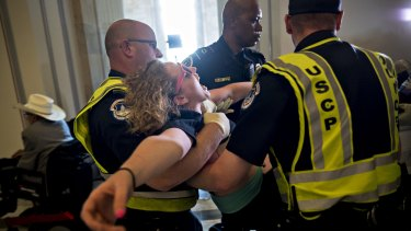 A demonstrator protesting cuts to Medicaid is carried away from the office of Senate Majority Leader Mitch McConnell at the Russell Senate Office building in Washington.