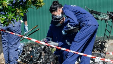 Police investigate the fire that killed three people.