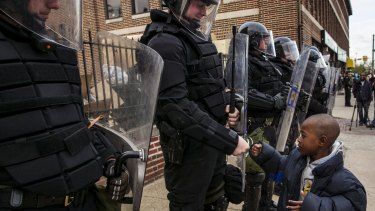 A young boy greets police officers in riot gear during a march in Baltimore after the decision to charge six officers, including one with murder.