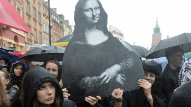 Dressed in black women carry a reproduction of the famous Leonardo Da Vinci painting, Mona Lisa, symbolising femininity, as they protest a proposed total ban on abortion.