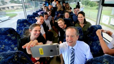 Opposition Leader Bill Shorten takes a selfie with media on the campaign bus.