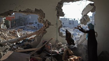 Sort through the rubble of a home destroyed during the Israel offensive in Gaza last August.