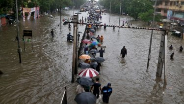 People walk through a waterlogged street following heavy rains in Mumbai, India, on Tuesday.