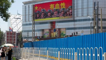 """People walk near a billboard of the Chinese military reading """"courageous"""", in Beijing, last month. Beijing is intensifying its warnings to Indian troops to get out of a contested region high in the Himalayas where China, India and Bhutan meet."""