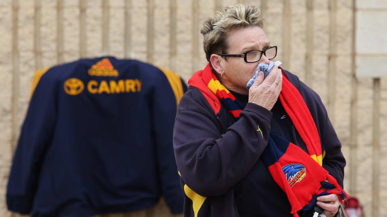 A Crows fan reacts after leaving flowers as a sign of remembrance to the late head coach Phil Walsh.
