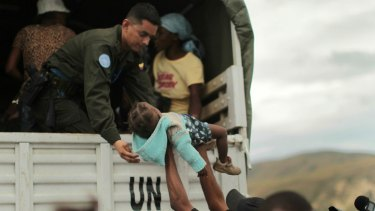 A UN peacekeeper is handed a child during an evacuation of vulnerable residents in Haiti in 2010.