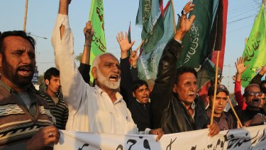 Pakistani protesters condemn a bombing at a Shiite mosque that targeted Friday prayers in Karachi, Pakistan.