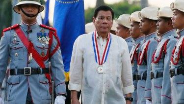 Philippine President Rodrigo Duterte reviews the troops as he leads a flag-raising ceremony in December.