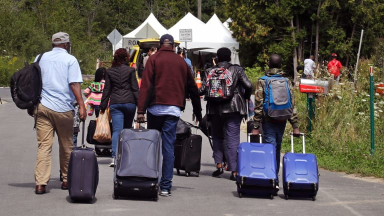 A family from Haiti approach a tent in Saint-Bernard-de-Lacolle, Quebec, stationed by Royal Canadian Mounted Police, as they haul their luggage down Roxham Road in Champlain, NY.