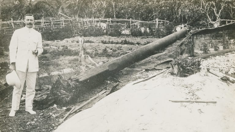 TENNIS COURT UNDAMAGED: The wireless operator who sent the SOS call that brought HMAS Sydney to the area, standing next to the wireless mast destroyed by the German raiding party from the Emden.