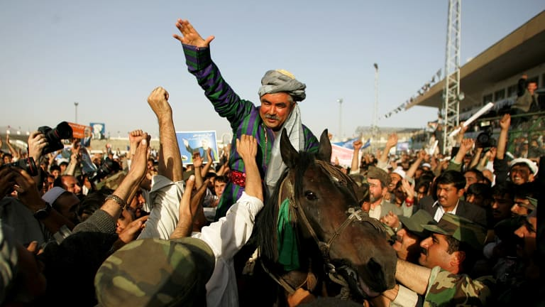 Then Afghan presidential candidate Abdul Rashid Dostum waves to supporters at a campaign rally in Kabul in 2004.