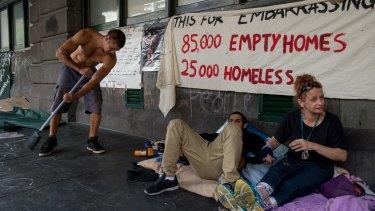 A homeless man keeps the footpath clean outside Flinders street station.