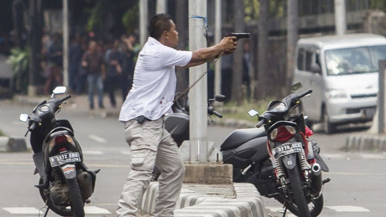 A plain-clothes police officer aims his gun at attackers during a gun battle following explosions in Jakarta.