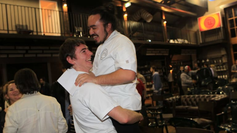 <i>MasterChef</i> winner Adam Liaw is picked up by second-place winner Callum Hann at the celebrations party.