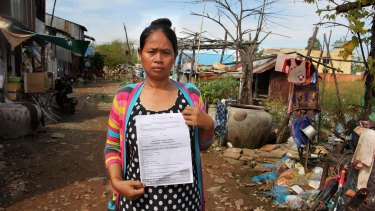 Cambodian surrogate mother Hour Vanny, holding the two-page document she signed with Fertility Solutions, operated by Australian nurse Tammy Davis-Charles.