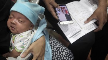 A parent with her child's vaccine record book at Harapan Bunda hospital in Jakarta.