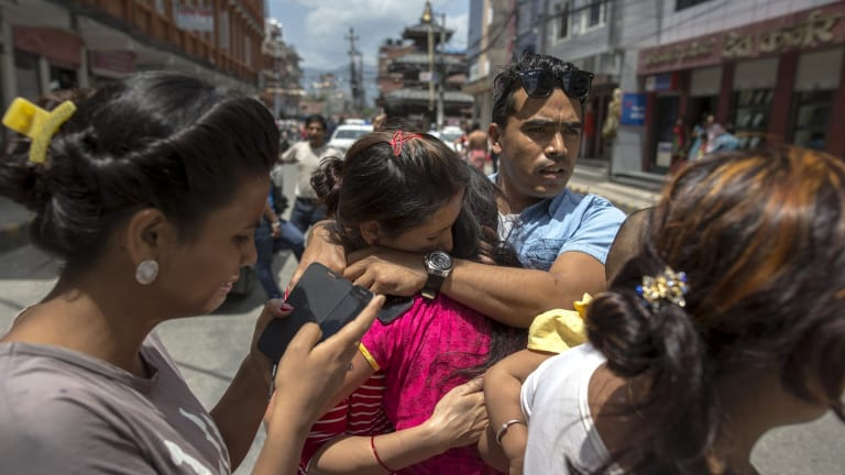 Local residents comfort each others during an earthquake in central Kathmandu.