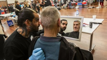 Picture of you: Barber Nasir Sobhani  gives homeless man Max a haircut at a volunteer-run Christmas on the Streets event in the Drill Hall in the city on Sunday.