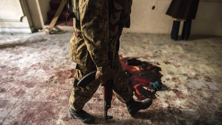 A soldier walks past blood on the auditorium floor at the Army Public School, which was attacked by Taliban gunmen.