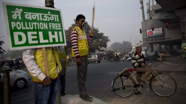 Volunteers display placards reading: 'We will make a pollution free Delhi' during a two-week experiment to reduce the number of cars to fight pollution in India, in January.