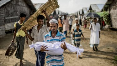 Noor Bashar carries the body of his one-year-old nephew, Mohamad Noor, for burial at a camp for Rohingya in Sittwe, Myanmar, in June 2015.