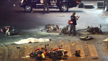 Carnage ... A policeman photographs debris from an explosion in central Bangkok, Thailand.