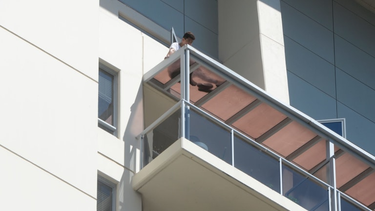 A man on top of a balcony in Chatswood after a woman's body was found below.