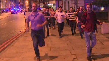 A man holds his beer while people flee terror attacks in London on Saturday.