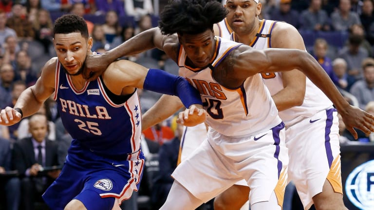 Phoenix Suns forward Josh Jackson, front right, battles with Philadelphia 76ers guard Ben Simmons (25) for a loose ball as Suns forward Jared Dudley, back right, watches.