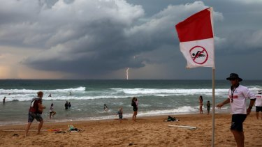 Wollongong City Council Lifeguard Jake Spooner raises the no swim flag, closing Austinmer beach as a Southerly storm moves up the coast.