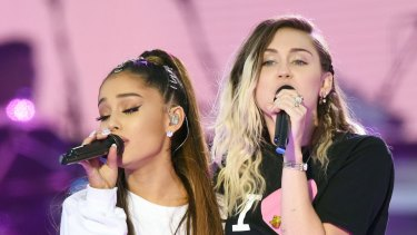 Ariana Grande, left, and Miley Cyrus perform at the One Love Manchester tribute concert in Manchester, England, Sunday, June 4, 2017.