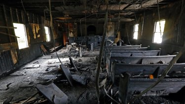 Burnt pews, destroyed musical instruments, Bibles and hymnals are part of the debris inside the fire damaged Hopewell MB Baptist Church in Greenville, Mississippi.