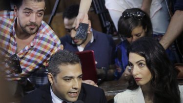 Canadian Al-Jazeera English journalist Mohammed Fahmy, left, his lawyer Amal Clooney and his Egyptian colleague Baher Mohammed, at top left, speak to media before their verdict in a courtroom in Cairo.