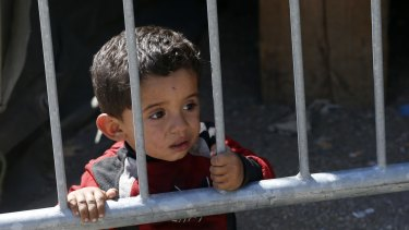 A child looks through the fence next to a migrant processing centre in the southern Serbian town of Presevo on Monday.
