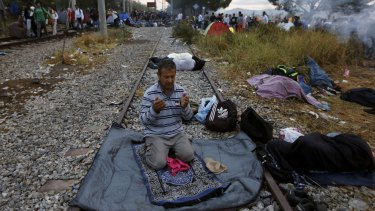 A Syrian refugee prays on a rail track at the Greek-Macedonian border.