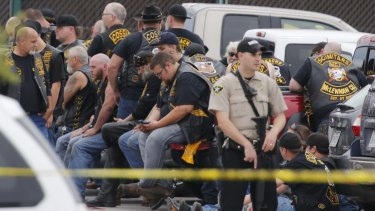 A McLennan County deputy stands guard near a group of bikers in Waco.