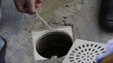 A government health agent puts larvicides into a sewage pipe inside a home during an operation to kill Aedes aegypti mosquitos in Rio de Janeiro, Brazil.