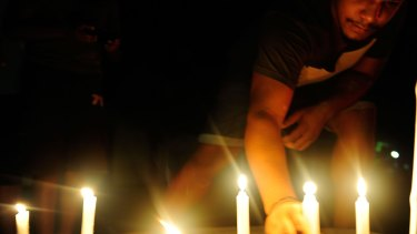 A candlelight vigil is held in the street where eight children died in a multiple stabbing in the suburb of Manoora.