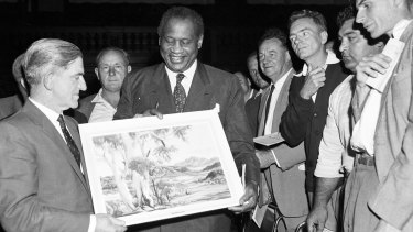 Robeson is presented with an Albert Namatjira painting during a mass meeting of waterside workers at Sydney Town Hall on 11 November 1960
