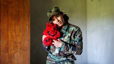 Asema Dahir, 21, poses with a teddy bear in a bedroom at a site near the frontline of the fight against Islamic State.
