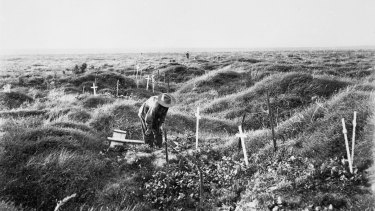 An Anzac soldier scrutinises a grave near Pozieres, along the line of OG1 trench in 1917, the year after the battle for Pozieres.