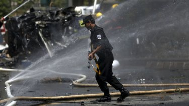 A policeman walks at the site of a car bomb blast at the entrance gate to the Kabul airport on Monday.