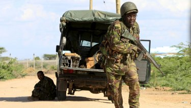 A Kenya Defence Force soldier runs for cover near the perimeter wall of Garissa University College.