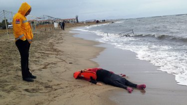 A Turkish rescue worker looks at the body of a migrant lying on the beach in Ayvalik.