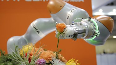 A robot arranging flowers at the International Robot exhibition in Tokyo last year.
