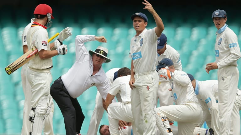 Umpires and players call for help as Hughes hit the ground.